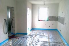 14) Po pokládce podlahového polystyrenu je možné položení separační folie a instalace rozvodů podlahového topení. V prostoru kuchyňské linky je vynechán pruh v povrchové štukové úpravě pro budoucí lepení keramického obkladu.